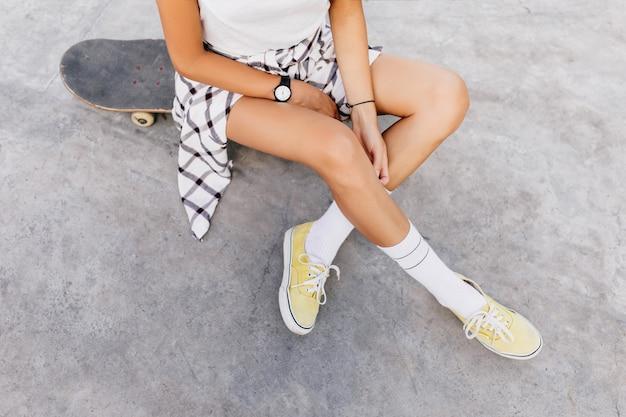 Fotografía aérea de mujer caucásica bronceada escalofriante en el parque de patinaje después del entrenamiento. magnífica mujer lleva calcetines blancos y zapatos amarillos sentado en patineta.