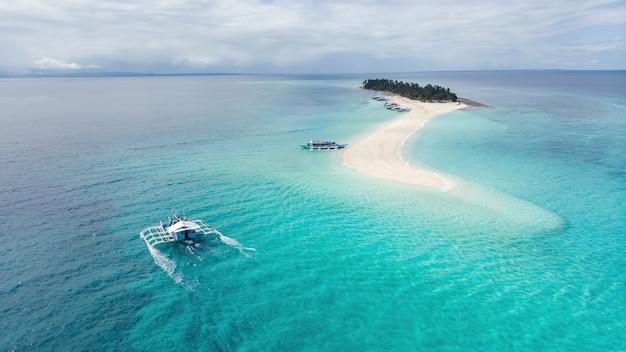 Fotografía aérea de un típico barco filipino que llega a una isla tropical paradisíaca