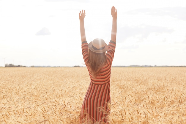 Fotografía al aire libre de una mujer joven alta y positiva que levanta sus brazos hacia el sol