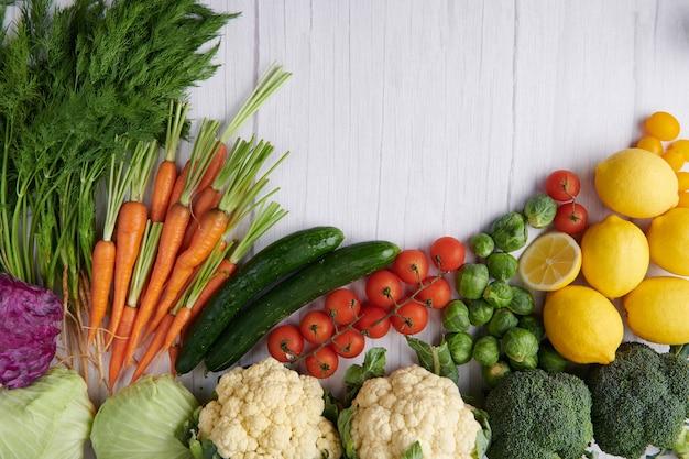 Fotografía de alimentos diferentes frutas y verduras en la superficie de la mesa de madera blanca.
