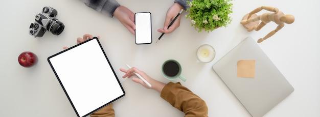 Fotografía de arriba de dos mujeres diseñadoras gráficas que consultan sobre su proyecto en un espacio de trabajo moderno