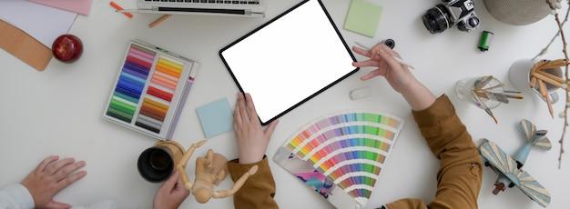 Fotografía de arriba del equipo de diseñadores trabajando juntos en una sala de reuniones mínima con tableta simulada, computadora portátil y suministros de diseño