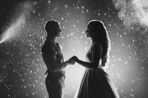 Fotografía en blanco y negro de la alegre novia y el novio tomados de la mano y sonriendo el uno al otro contra los fuegos artificiales brillantes