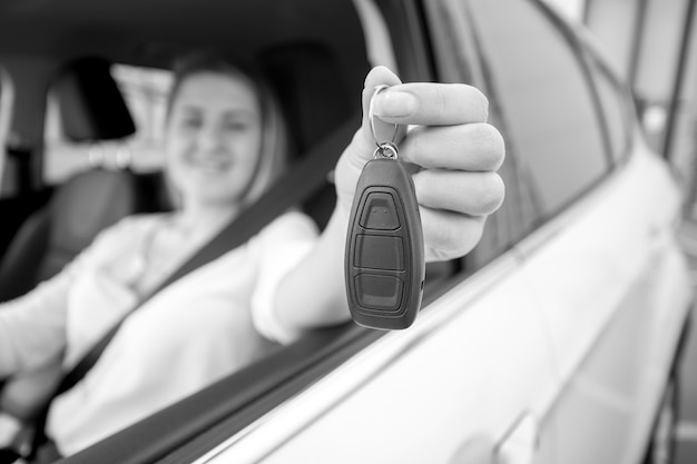 Fotografía en blanco y negro de mujer feliz mostrando las llaves del coche a través de la ventana abierta