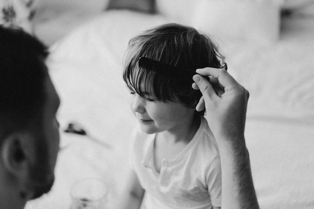 Fotografía en blanco y negro. padre le corta el pelo a su hijo en la habitación