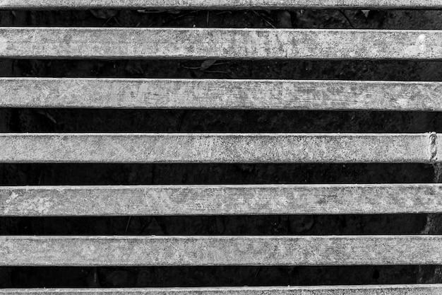 Fotografía en blanco y negro de rejilla de hierro sobre el canal de drenaje en la carretera