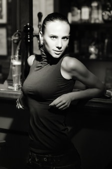 Fotografía en blanco y negro de yang y hermosa mujer de pie junto al soporte de la barra