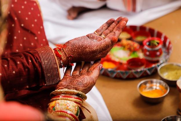 Fotografía de boda india, novio y novia de manos.