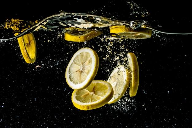 Fotografía de bodegones de rodajas de limón cayendo bajo el agua y haciendo un gran revuelo