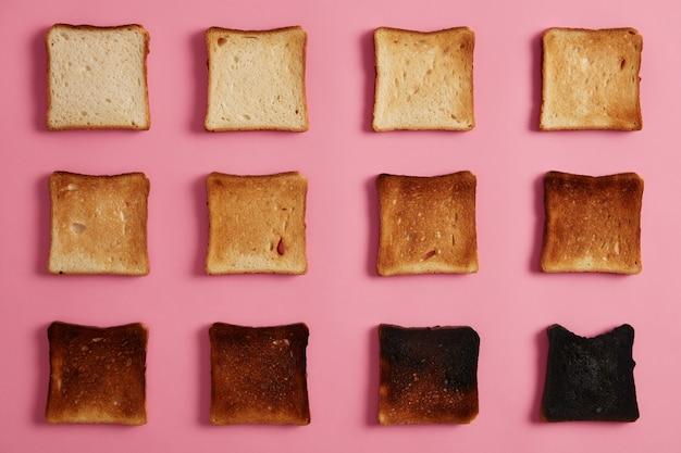 Fotografía cenital aislada de tostadas de pan en diferentes etapas de tueste contra un fondo rosado. la última rebanada está completamente quemada. refrigerio para el desayuno. de tostado a carbonizado. fotografía gastronómica