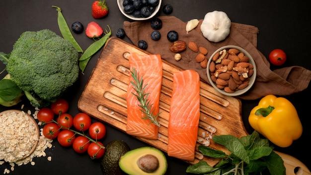 Fotografía cenital de alimentos sanos, surtido de selección de comidas limpias con salmón, frutas, verduras, semillas y espacio de copia