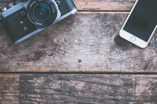 Fotografía cenital de una cámara y un teléfono inteligente sobre un fondo de madera marrón