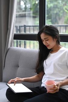 Fotografía cenital de casual joven sentado en el sofá en la sala de estar con teléfono inteligente y tomando café.