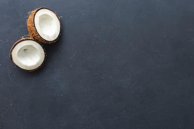 Fotografía cenital de cocos cortados sobre un fondo gris, perfecto para papel tapiz