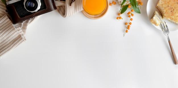 Fotografía cenital de cómodo espacio de trabajo con cámara y desayuno en mesa blanca con espacio de copia