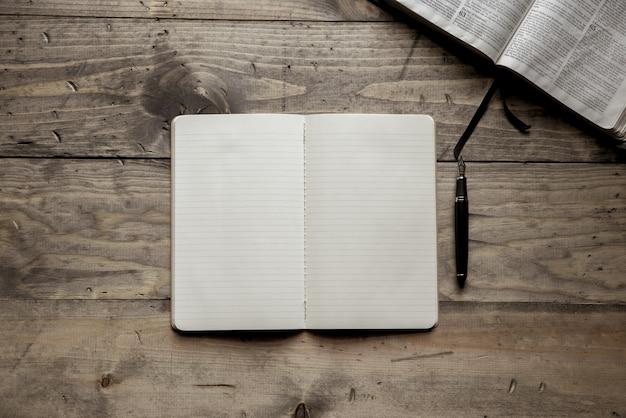 Fotografía cenital de un cuaderno en blanco cerca de una pluma estilográfica sobre una superficie de madera