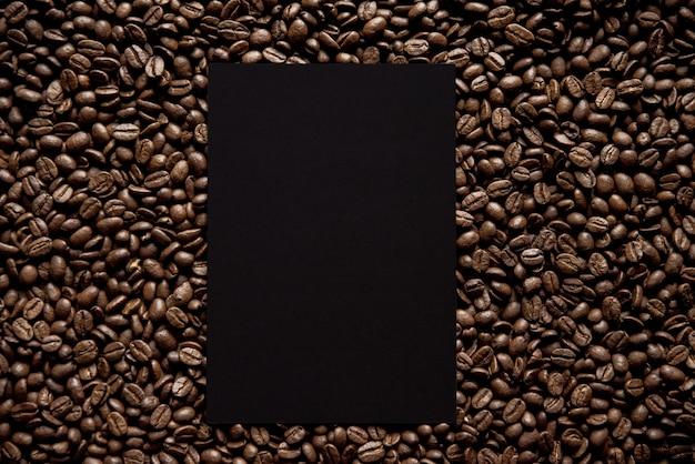 Fotografía cenital de un cuadrado negro en medio de granos de café ideal para escribir texto