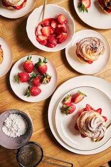 Fotografía cenital de delicioso hojaldre de crema con fresas y chocolate en una mesa de madera