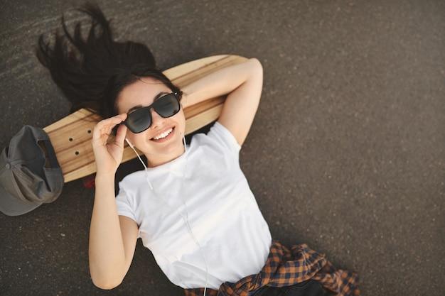 Fotografía cenital despreocupada adolescente tumbado sobre hormigón en skatepark