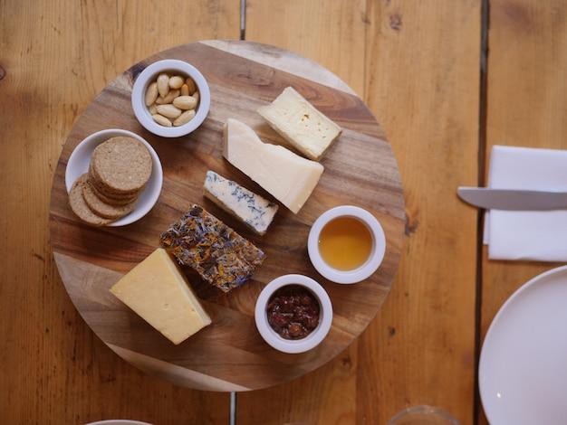 Fotografía cenital de diferentes quesos en una bandeja redonda de madera con diferentes salsas y galletas
