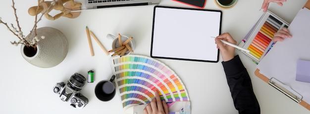 Fotografía cenital del diseñador trabajando en una tableta digital simulada, suministros de diseño y decoraciones