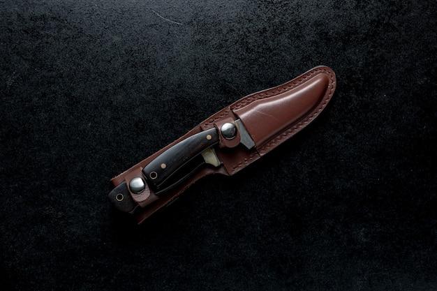 Fotografía cenital de dos cuchillos fijos con mango marrón en un estuche marrón sobre tabla negra