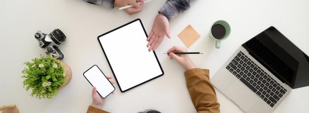Fotografía cenital de dos diseñadoras gráficas discutiendo sobre su proyecto en el espacio de trabajo moderno