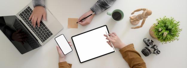 Fotografía cenital de dos diseñadores gráficos femeninos que intercambian ideas sobre su proyecto en una mesa blanca