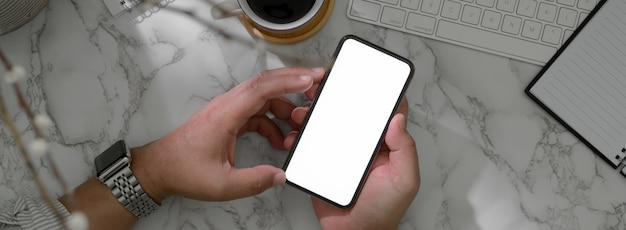 Fotografía cenital del empresario masculino con un teléfono inteligente de pantalla en blanco para relajarse en la mesa de trabajo de mármol