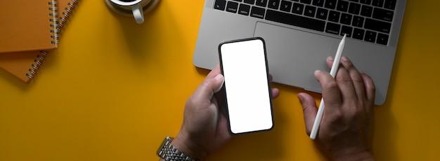 Fotografía cenital del empresario que trabaja con la pantalla en blanco de teléfonos inteligentes y portátiles