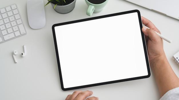 Fotografía cenital del empresario que trabaja en la tableta en el moderno espacio de trabajo con computadora, computadora portátil y suministros de oficina