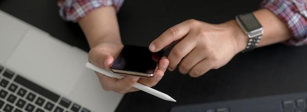Fotografía cenital del empresario tocando el teléfono inteligente mientras trabaja con dispositivos digitales