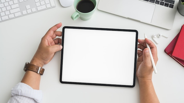 Fotografía cenital del empresario trabajando en tableta en el espacio de trabajo con computadora, computadora portátil y otros suministros de oficina