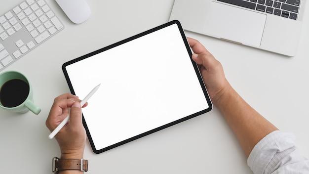 Fotografía cenital del empresario trabajando en tableta en un práctico espacio de trabajo con computadora y laptop