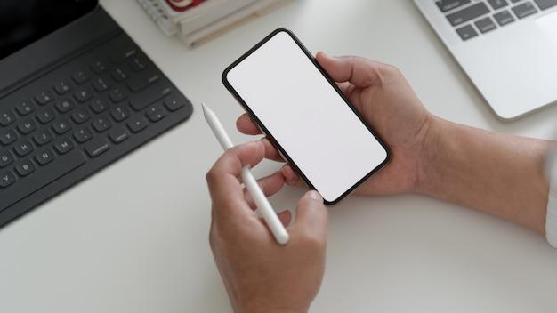 Fotografía cenital del empresario usando el teléfono en el espacio de trabajo con computadora portátil, tableta y otros suministros de oficina
