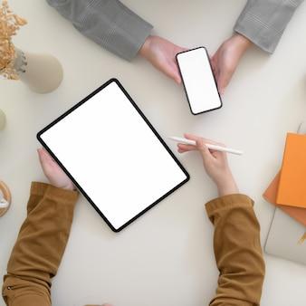 Fotografía cenital de empresarios discutiendo sobre su proyecto con dispositivos digitales