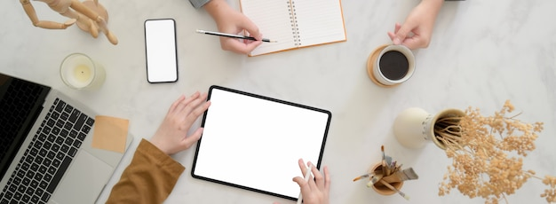 Fotografía cenital de empresarios haciendo una lluvia de ideas sobre su proyecto en un escritorio de oficina blanco