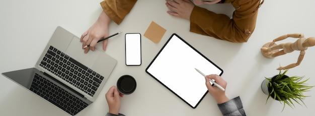 Fotografía cenital de empresarios que consultan sobre su estrategia comercial en la mesa blanca
