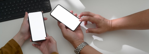Fotografía cenital de empresarios que consultan sobre su trabajo con teléfonos inteligentes
