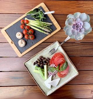 Fotografía cenital de ensalada con frijoles y queso en un plato cerca de una bandeja de madera con vegetales cerca de rosa