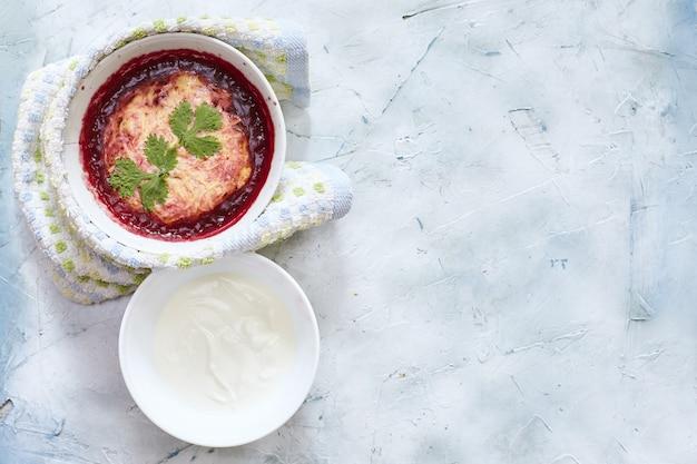 Fotografía cenital de una ensalada con puré de papas, tomate y salsa blanca