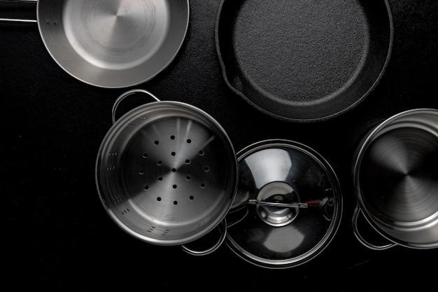 Fotografía cenital en escala de grises de una sartén olla de metal una tapa
