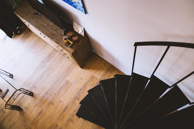 Fotografía cenital de escaleras de caracol negras cerca de un cajón con un televisor en la parte superior