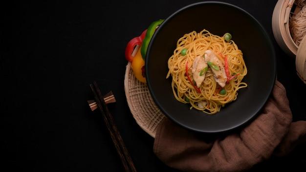 Fotografía cenital de fideos schezwan con salsa de vegetales, pollo y chile