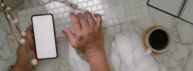 Fotografía cenital de hombre empresario trabajando con teclado de computadora, teléfono inteligente