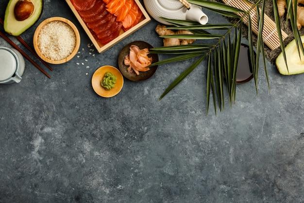 Fotografía cenital de ingredientes para sushi sobre fondo azul oscuro