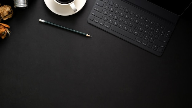 Fotografía cenital del lugar de trabajo moderno y oscuro con teclado inalámbrico, espacio de copia, cámara y taza de café en la mesa negra