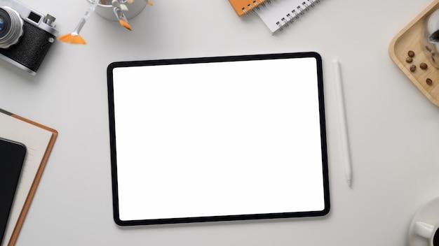 Fotografía cenital del lugar de trabajo con pantalla en blanco portátil, pincel y útiles de oficina en mesa blanca