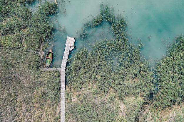 Fotografía cenital de un muelle de madera en la costa con un barco de pesca al lado