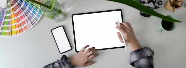 Fotografía cenital de una mujer freelance que trabaja con una tableta de pantalla en blanco y un teléfono inteligente